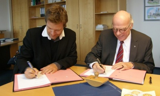 Bishop Gerhard Ulrich and Minister Robert Habeck signing the agreement