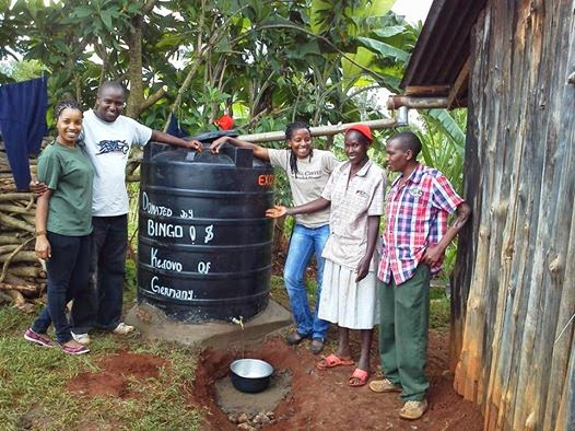 Muthoni and the Kedovo gang posing next to their newly installed water tank