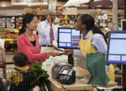 Mother and son paying cashier at supermarket