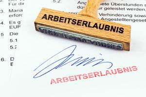 Holzstempel auf Dokument: Arbeitserlaubnis